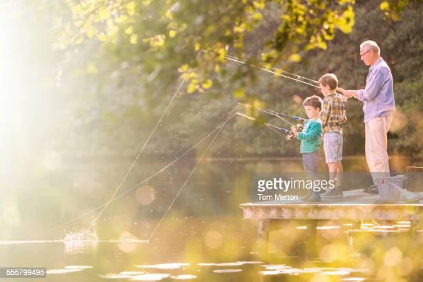 Grandfather and grandsons fishing at lake