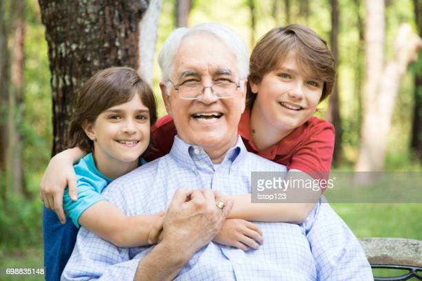 Grandfather and grandsons hugging outdoors together.