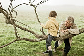 Grandfather and his grandson playing on a tree