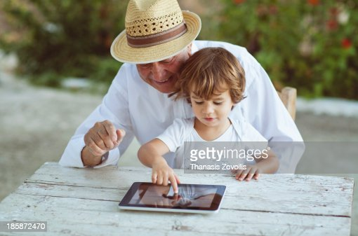 Grandfather and his grandson playing with a tablet