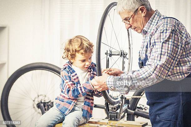 Grandfather and his grandson repairing a bicycle