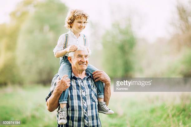 Grandfather and his grandson walking outdoors