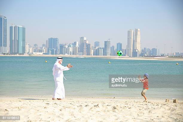 Grandfather and little boy playing ball on the beach