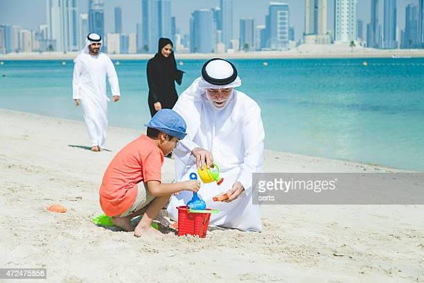 Grandfather and little boy playing on the beach