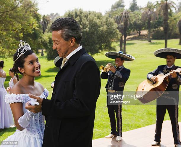 Grandfather and teenage girl dancing at quinceanera