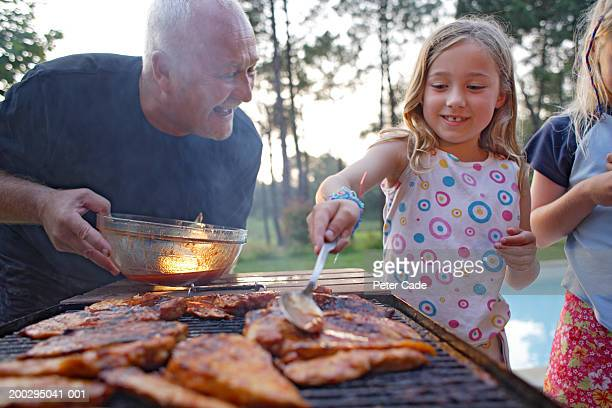 Grandfather and two girls (7-11) barbecuing