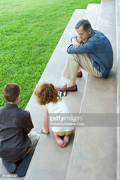 Grandfather and two grandchildren playing with toy cars together on stairs, high angle view
