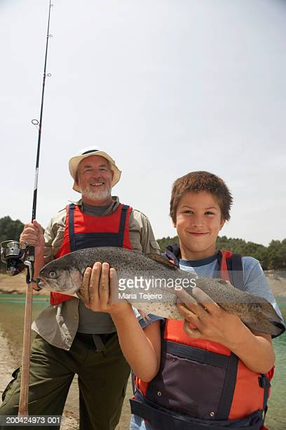 Grandfather behind boy (5-7) holding up large caught fish, portrait