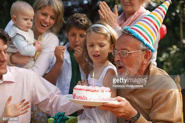 Grandfather blowing out candles at party