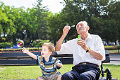 grandfather blowing soap bubbles to grandchild in a park in summer sunny day