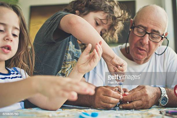Grandfather building a robot with his grandchildren.