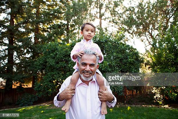 Grandfather carrying grandson on shoulders in backyard