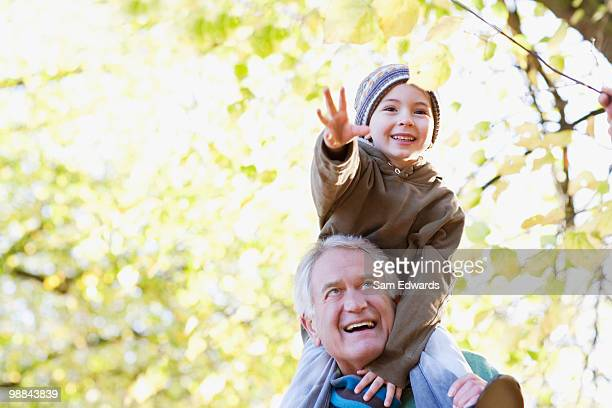 Grandfather carrying grandson on shoulders