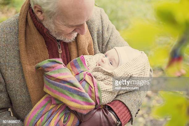 Grandfather cradling grandson, high angle