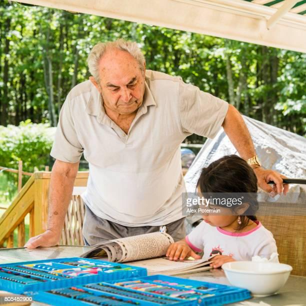 Abuelo, anciano pero activo hombre senior, 90 años de edad, viendo cómo su nieta dibujo