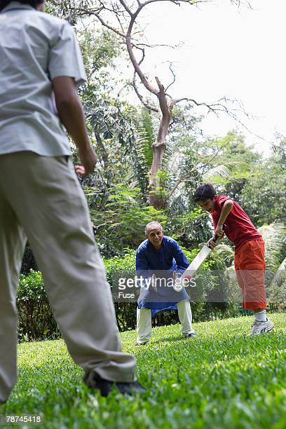 Grandfather, Father and Boy Playing Cricket in Park