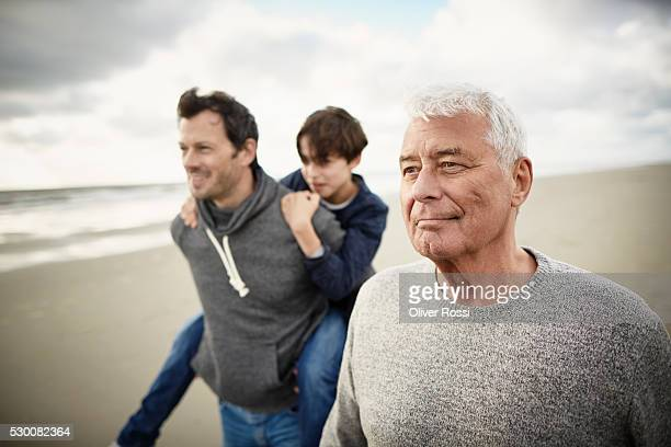 Grandfather, father and son on the beach
