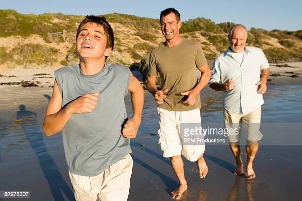 Grandfather, father and son running on beach