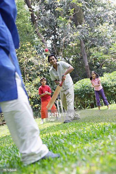Grandfather, Father and Two Children Playing Cricket in Park