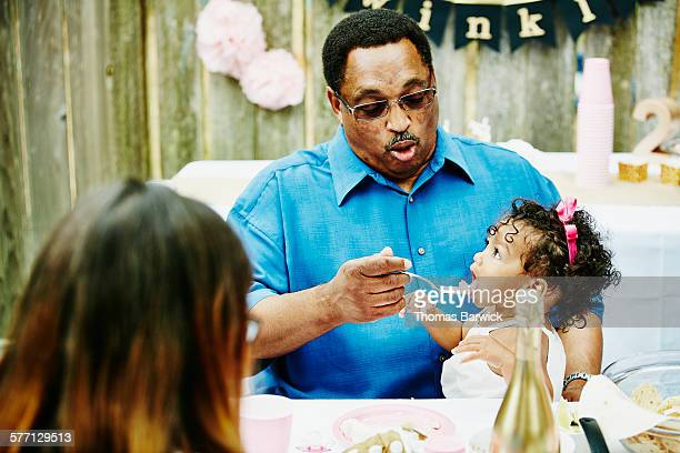 Grandfather feeding granddaughter cake at party