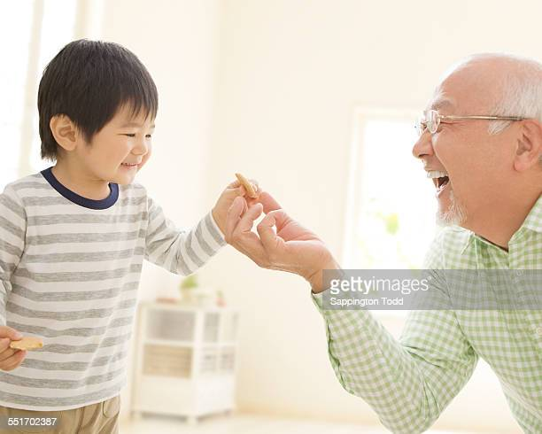 Grandfather Giving Candy To Grandson