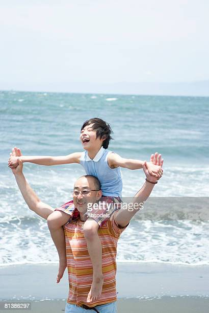 Grandfather giving his grandson (8-9) a piggyback on beach, arm raised