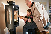 Grandfather & grandson building a fire