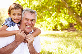 Grandfather having fun outdoors with his grandson, portrait, smiling to camera