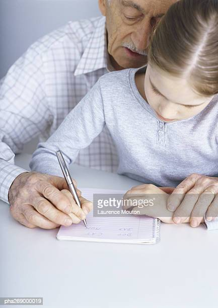 Grandfather helping girl write in notebook