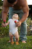 Grandfather helping granddaughter to walk holding rattles