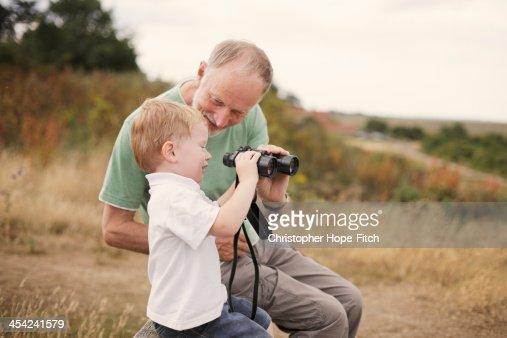 Grandfather helping grandson : Stock Photo