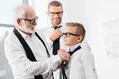 grandfather helping his grandson tie a necktie, while father is watching