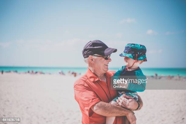 Grandfather Holding Baby Boy on Tropical Beach, Cuba