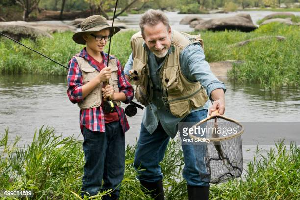Grandfather holding fish in net for grandson