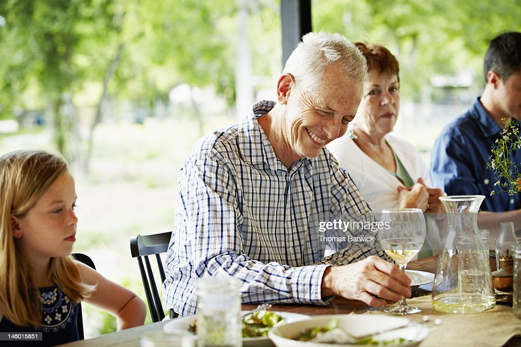 Grandfather holding glass of wine laughing : Stock Photo