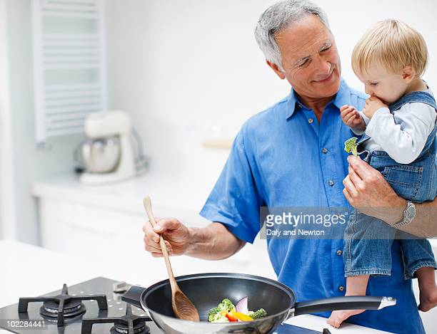 Grandfather holding grandson and cooking