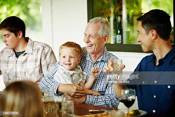 Grandfather holding grandson on lap at table