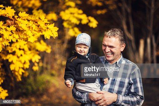 grandfather holding his grandchild on arm, autumn : Stock Photo