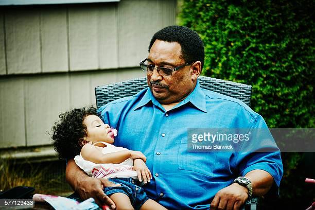 Grandfather holding sleeping toddler granddaughter
