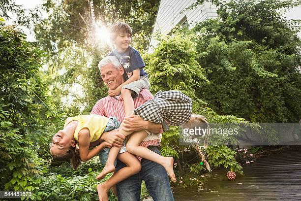 Grandfather holding three grandchildren