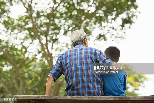 Grandfather hugging his grandson in park