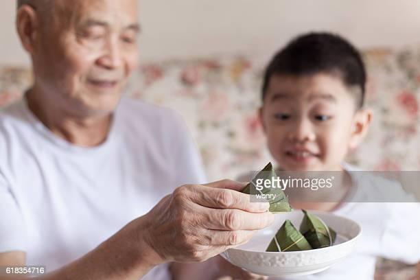 Grandfather introducing grandson to zongzi