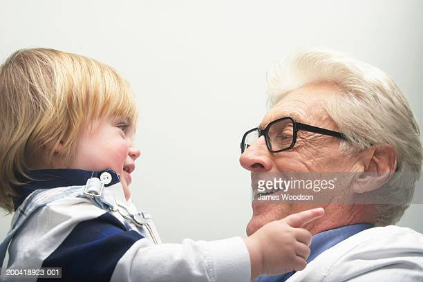 Grandfather lifting granddaughter (12-15 months), side view, close-up