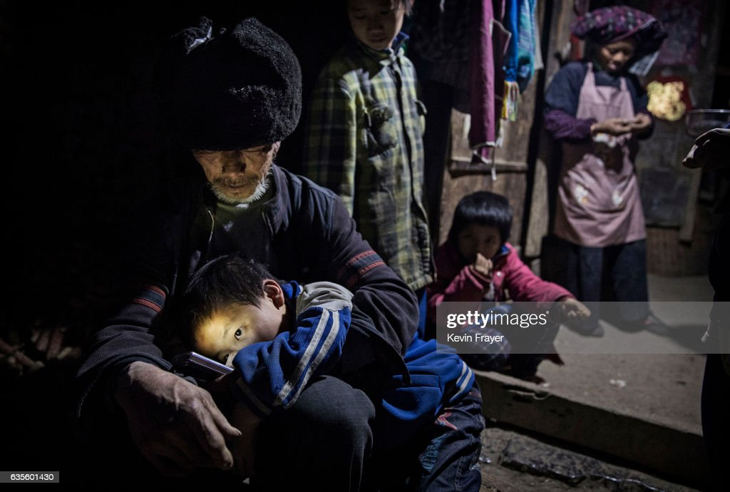 Luo Jie's grandfather Luo Yingtao, 64, holds Jie in his lap as they sit at the family house. In the case of the Luo grandparents, who are elderly and poor, they do what they can to meet the basic needs of four children between the ages of 5 and 11. Photo by Kevin Frayer/Getty Images