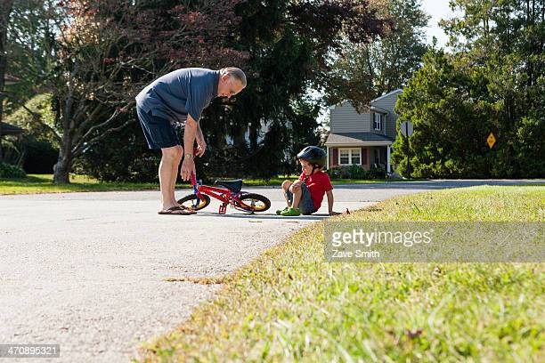 Grandfather picking up young boys bicycle