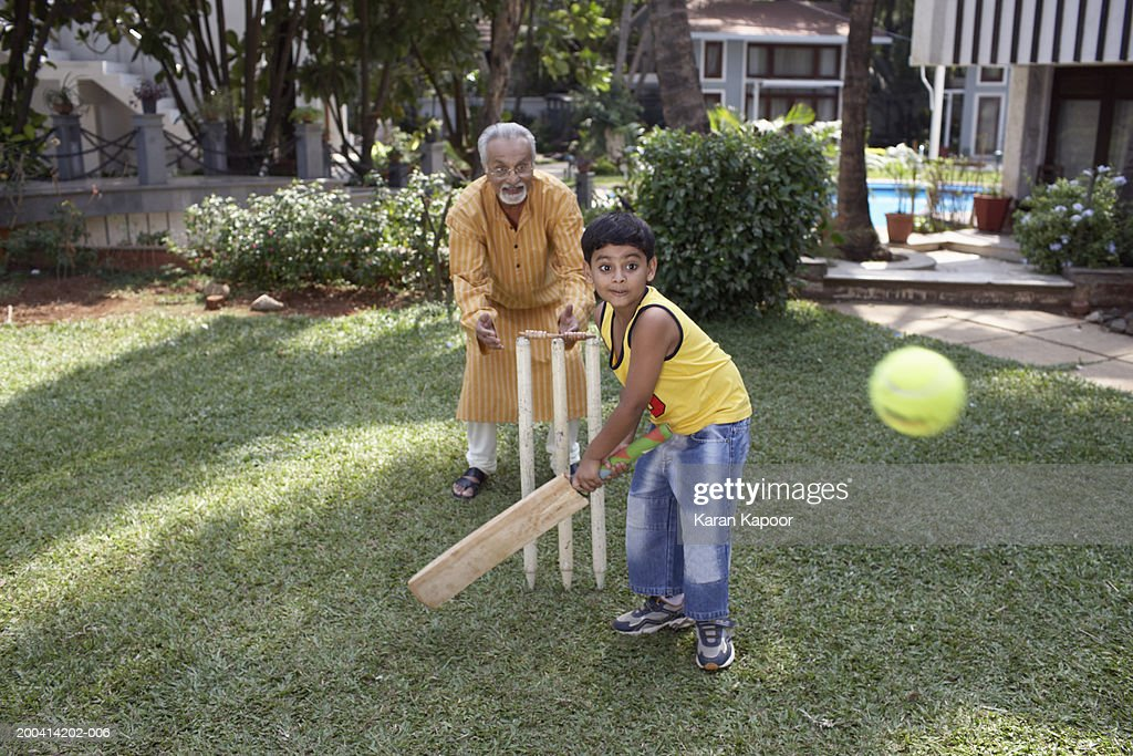 Grandfather playing cricket with grandson (6-8) batting ball