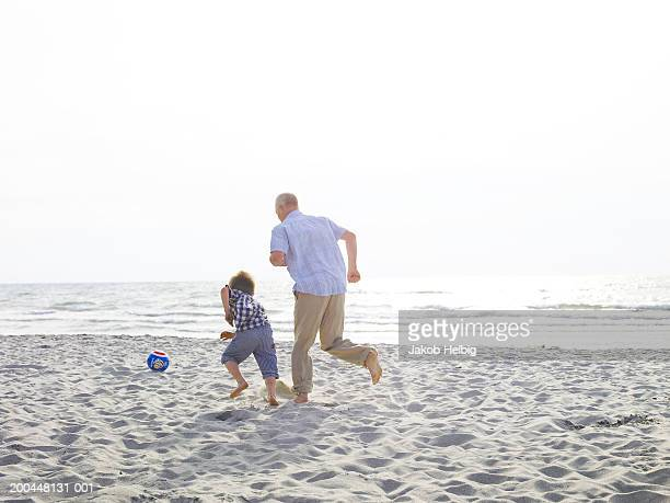Grandfather playing football on beach with grandson (4-6) rear view