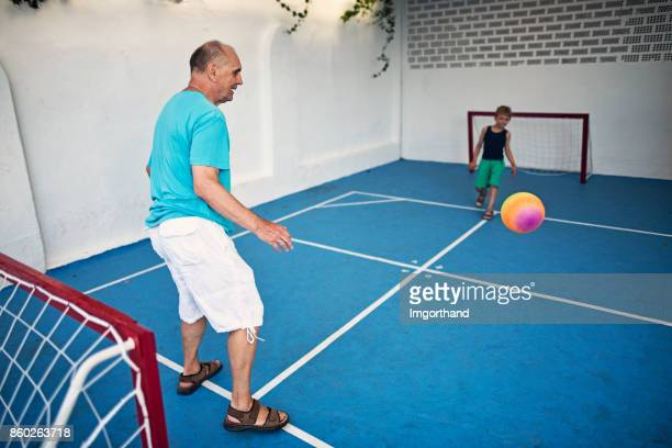 Grandfather playing football with grandson