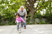 Grandfather playing hopscotch with toddler granddaughter