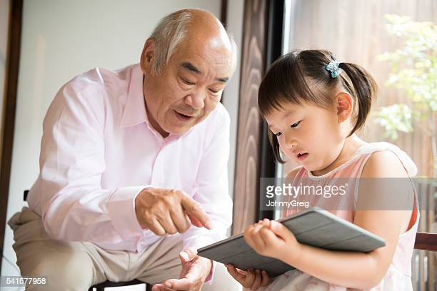 Grandfather pointing at digital tablet with Japanese granddaughter